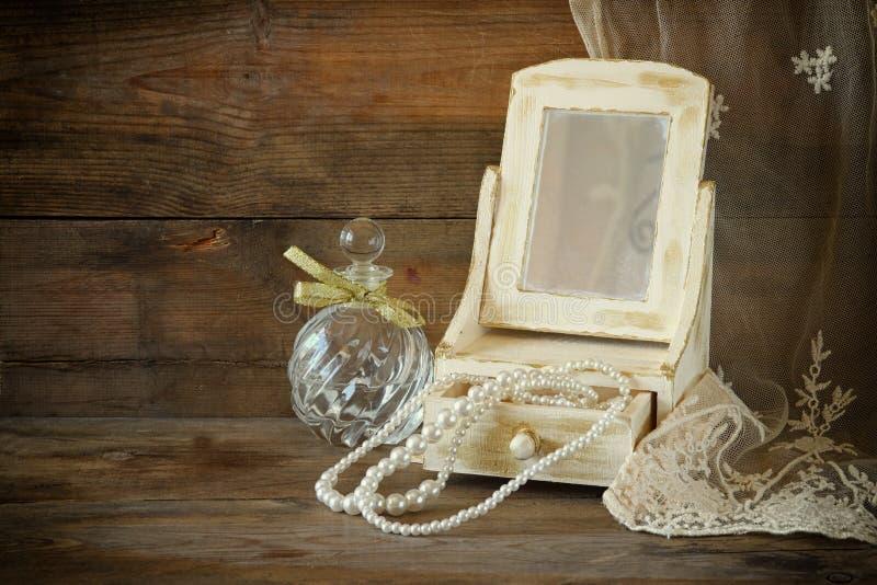 葡萄酒珍珠、古色古香的木首饰盒有镜子的和香水瓶在木桌上 被过滤的图象 免版税库存照片