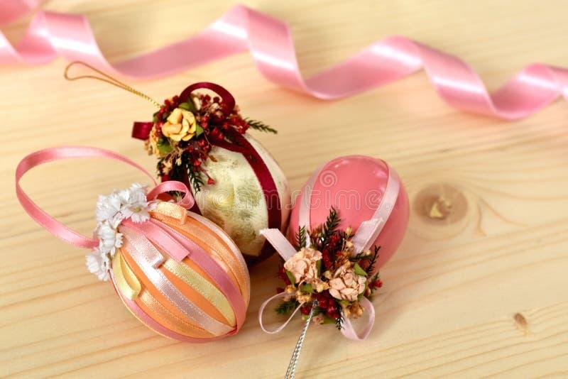 葡萄酒用发光的丝带装饰的三个桃红色色的复活节彩蛋的复活节装饰 库存图片
