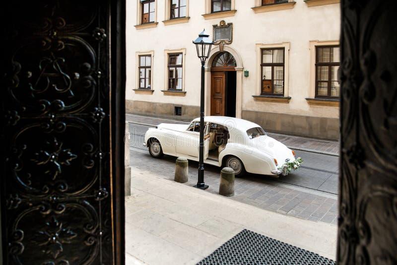 葡萄酒用花装饰的婚礼汽车在教会附近 免版税库存图片