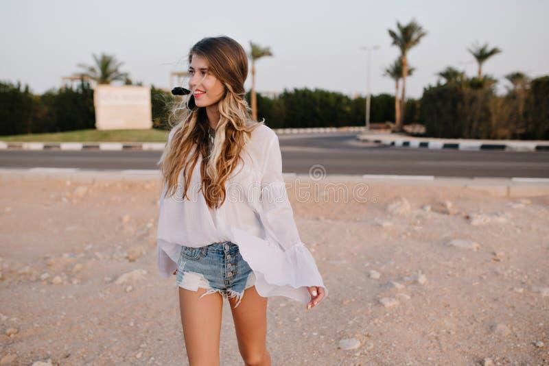 葡萄酒白色女衬衫的亭亭玉立的长发女孩走在与异乎寻常的棕榈树的沙子的在背景 迷住年轻 免版税库存照片