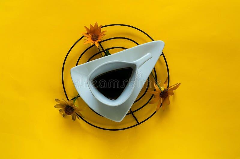 葡萄酒白色陶瓷杯子用咖啡 与延命菊花的创造性的背景在年的黄色纹理颜色的2019年 免版税库存图片