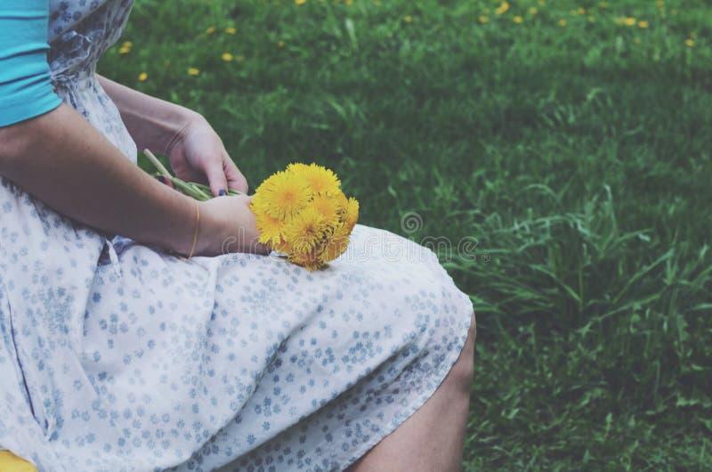 葡萄酒的坐的女孩穿戴拿着束黄色蒲公英 库存图片