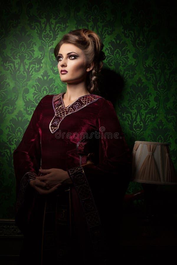 葡萄酒的妇女在绿色洛可可式的样式背景穿衣 库存照片
