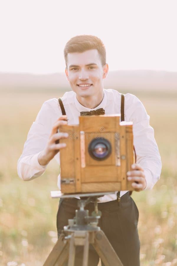 葡萄酒的特写镜头画象打扮了拍照片的新郎使用木老照相机在背景  免版税库存图片