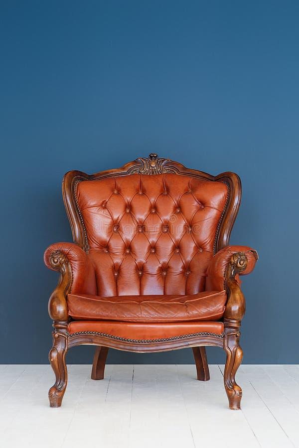 葡萄酒皮革豪华棕色扶手椅子经典布朗皮革沙发和老蓝色背景 免版税库存图片