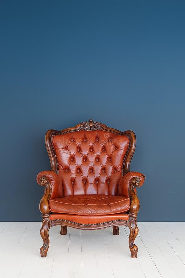 葡萄酒皮革豪华棕色扶手椅子经典布朗皮革沙发和老蓝色背景 免版税库存照片