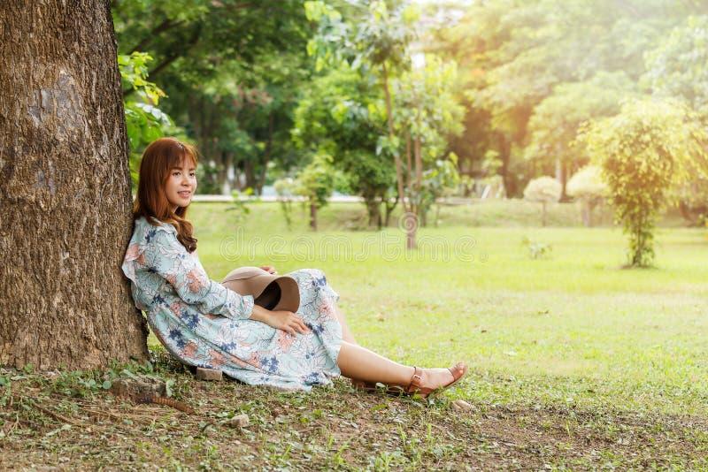 葡萄酒礼服坐的倾斜的俏丽的亚裔女孩反对在树放松 葡萄酒口气 库存图片
