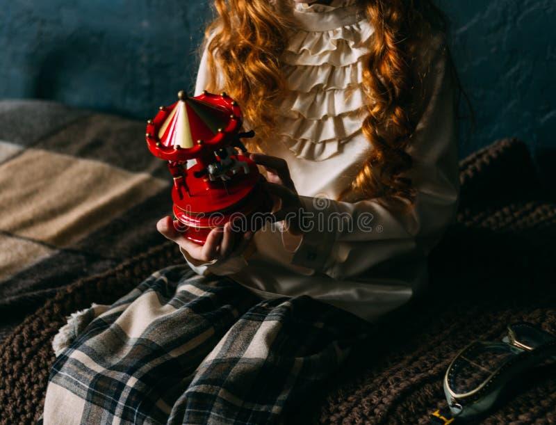 葡萄酒礼服的一个小女孩拿着一个红色玩具,旋转木马 不耐烦 免版税库存照片