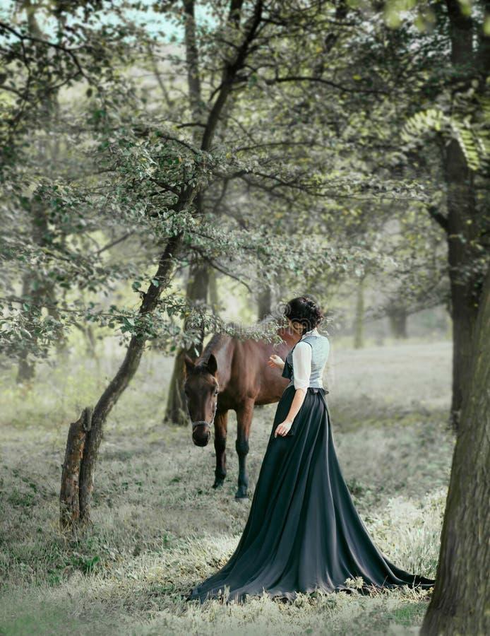 葡萄酒礼服的公主有一列长的火车的,走与马 一个深色的女孩的照片有后面的没有面孔 后面 免版税库存照片