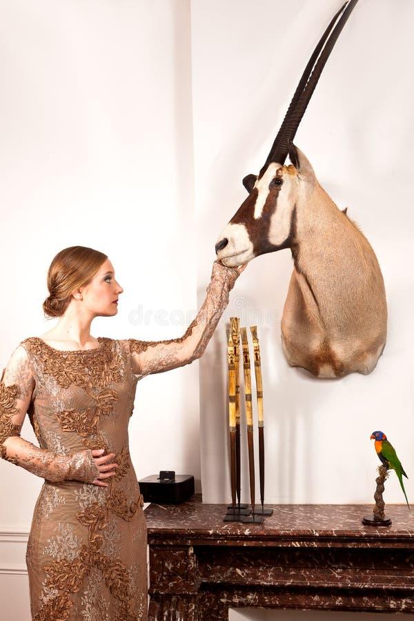 葡萄酒礼服的女孩有被充塞的羚羊属和鸟的 免版税库存图片