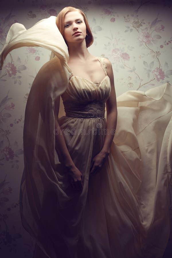 葡萄酒礼服的愉快的迷人的红发女孩 免版税库存图片