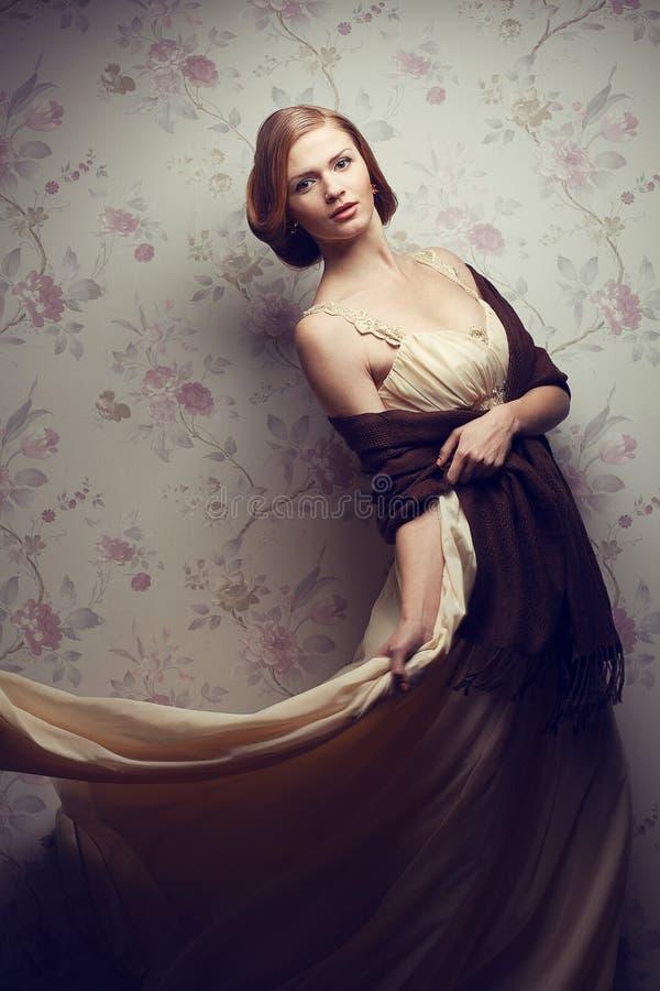 葡萄酒礼服的愉快的迷人的红发女孩 库存照片