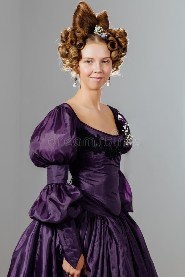 葡萄酒礼服的美丽的少妇有设计师头发的 球,平衡招待会 图库摄影
