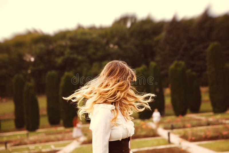 葡萄酒礼服的美丽的长发女孩走在夏令时公园的 图库摄影