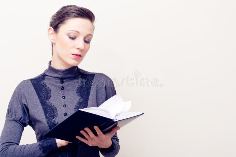 葡萄酒礼服读书圣经的年轻美丽的妇女 库存照片