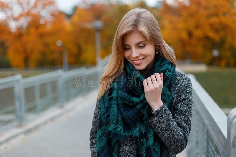 葡萄酒秋天时髦的外套的快乐的俏丽的年轻女人在街道上的一个时兴的方格的围巾身分 免版税库存照片