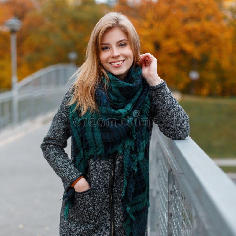 葡萄酒秋天时髦的外套的愉快的俏丽的逗人喜爱的年轻女人在一条时兴的绿色围巾站立户外 免版税图库摄影
