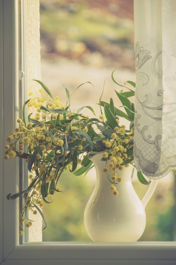 葡萄酒称呼了图象-有黄色花的投手在窗口 免版税库存图片