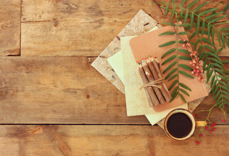 葡萄酒笔记本,老纸和黏附五颜六色的木铅笔在咖啡在木桌的旁边 为大模型准备 库存照片