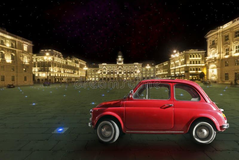 葡萄酒红色汽车在历史名城的里雅斯特,意大利 晚上 免版税库存照片