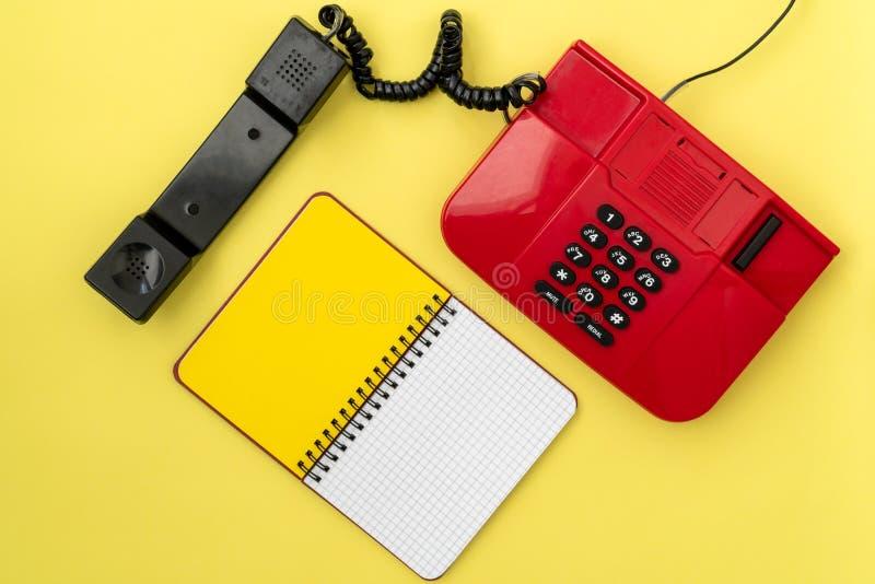 葡萄酒红色电话和空白的笔记本 免版税图库摄影