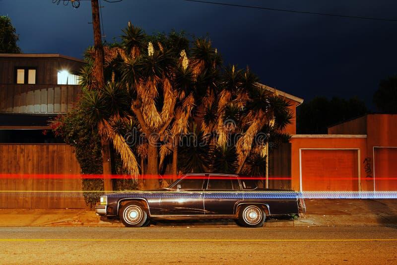 葡萄酒经典美国肌肉跑车搬运车的看法拾起卡车,并且光由在威尼斯海滩,加利福尼亚a的交通落后 图库摄影