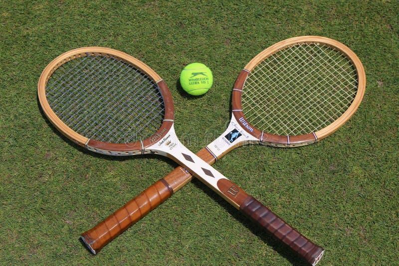 葡萄酒网球拍和Slazenger Wimbledon网球在草网球场 库存照片