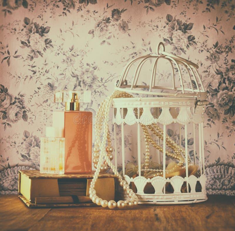 葡萄酒老珍珠项链和香水样式照片在花卉样式背景 减速火箭的被过滤的图象 图库摄影