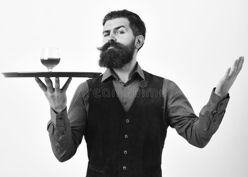 葡萄酒背心的侍者用威士忌酒或刻痕在盘子 有严密的面孔的男服务员供食科涅克白兰地 豪华饮料概念 库存照片