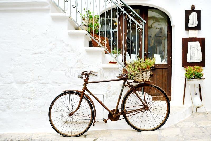 葡萄酒自行车对墙壁在白色城市奥斯图尼,普利亚,意大利-艺术性的图片意大利样式概念 免版税库存照片