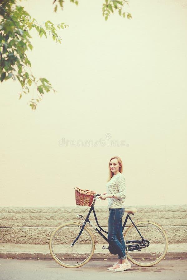 葡萄酒自行车的年轻白肤金发的妇女 免版税库存照片