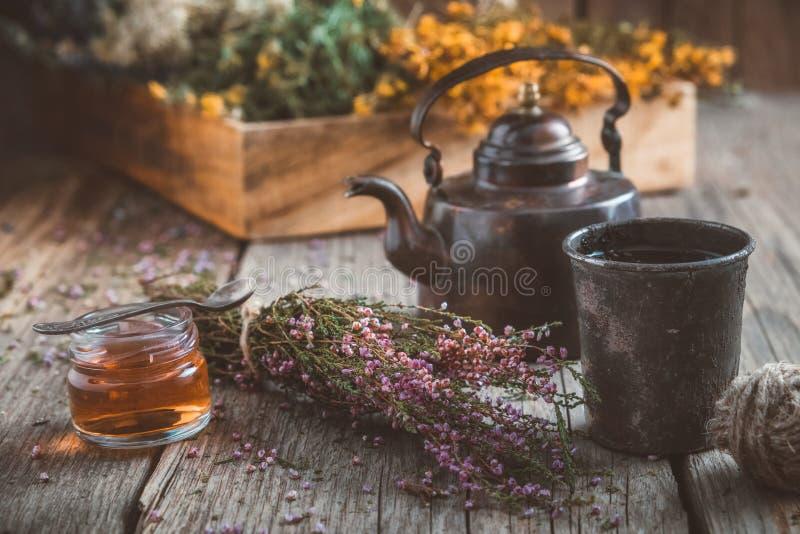 葡萄酒茶壶、杯子清凉茶,蜂蜜瓶子、石南花束和医药草本在背景 免版税图库摄影