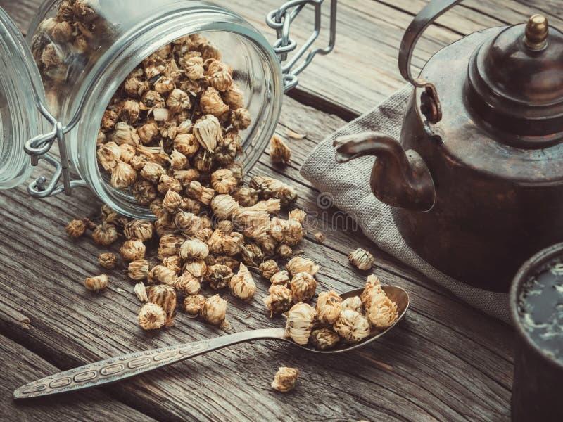 葡萄酒茶壶、玻璃瓶子干燥健康春黄菊芽,匙子和减速火箭的杯子在木桌上的雏菊清凉茶 库存图片
