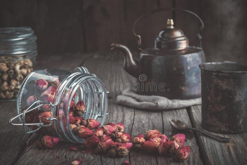 葡萄酒茶壶,杯子健康清凉茶和玻璃瓶子干玫瑰色芽和雏菊茶 免版税库存图片