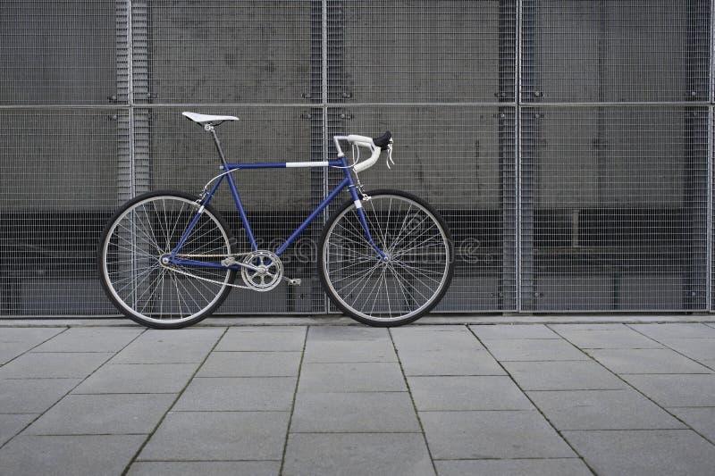 葡萄酒蓝色城市,有白色细节的路自行车 免版税库存照片