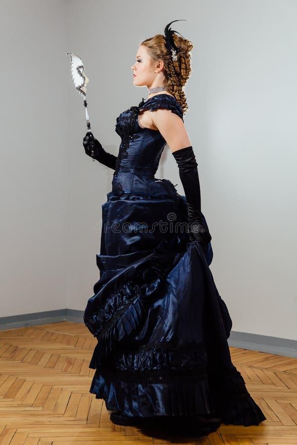 葡萄酒蓝色礼服的女孩有面具的在手上 角色的女演员 演员` s比赛 库存照片