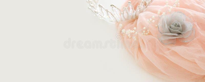 葡萄酒薄纱桃红色薄绸的礼服和金刚石冠状头饰在木白色桌上 婚礼和girl& x27; s党概念 免版税库存照片