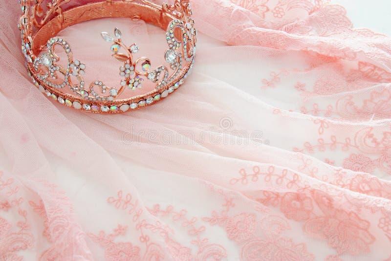 葡萄酒薄纱桃红色薄绸的礼服和金刚石冠状头饰在木白色桌上 免版税库存照片
