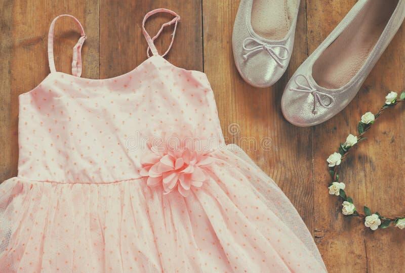 葡萄酒薄绸的女孩的礼服,在芭蕾舞鞋旁边的花卉冠状头饰 免版税库存照片