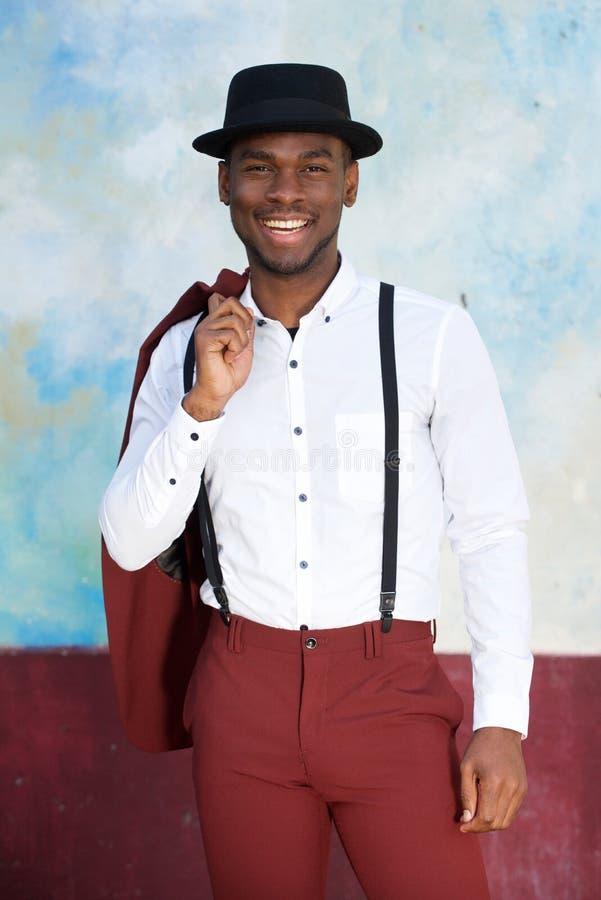 葡萄酒衣服的微笑由墙壁的英俊的年轻黑人和帽子 库存照片
