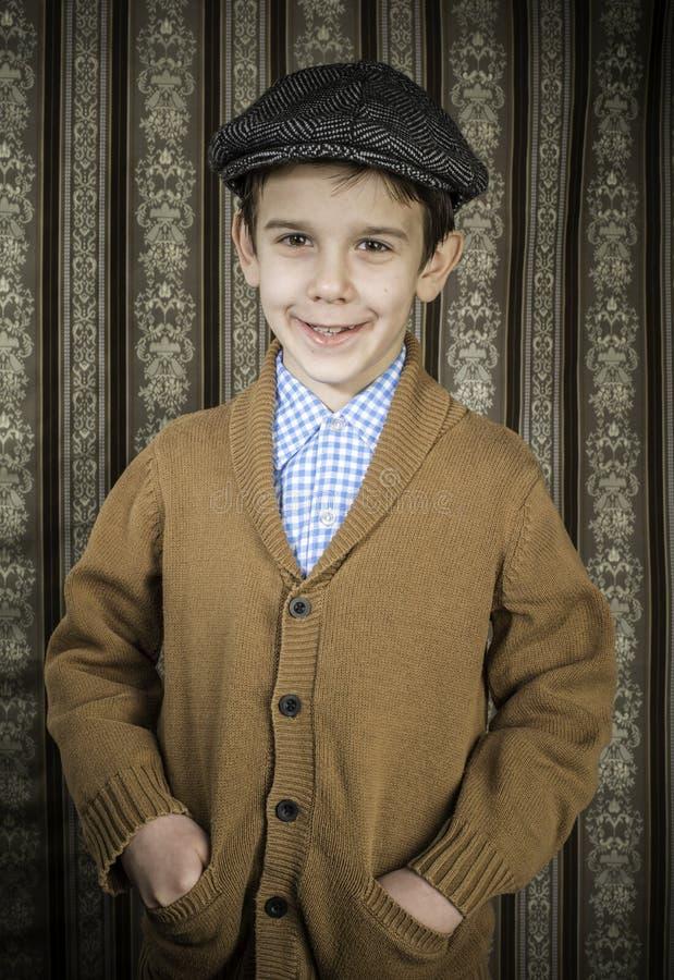 葡萄酒衣裳和帽子的微笑的孩子 库存图片