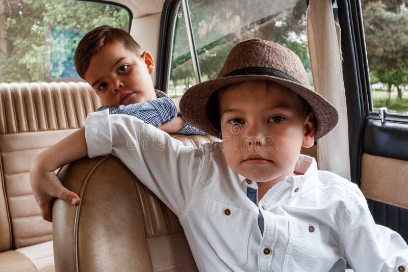 葡萄酒衣裳的两个小男孩在一辆减速火箭的汽车坐 免版税图库摄影