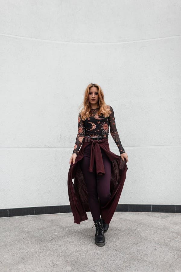 葡萄酒裤子的都市欧洲逗人喜爱的年轻女人有在一件时兴的被仿造的女衬衫的紫色海角的在鞋子摆在 免版税库存图片