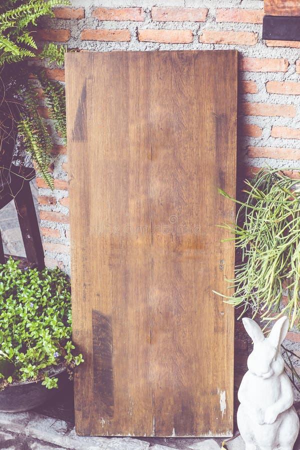 葡萄酒过滤器:在砖墙上的空的木标志板在前面 库存图片