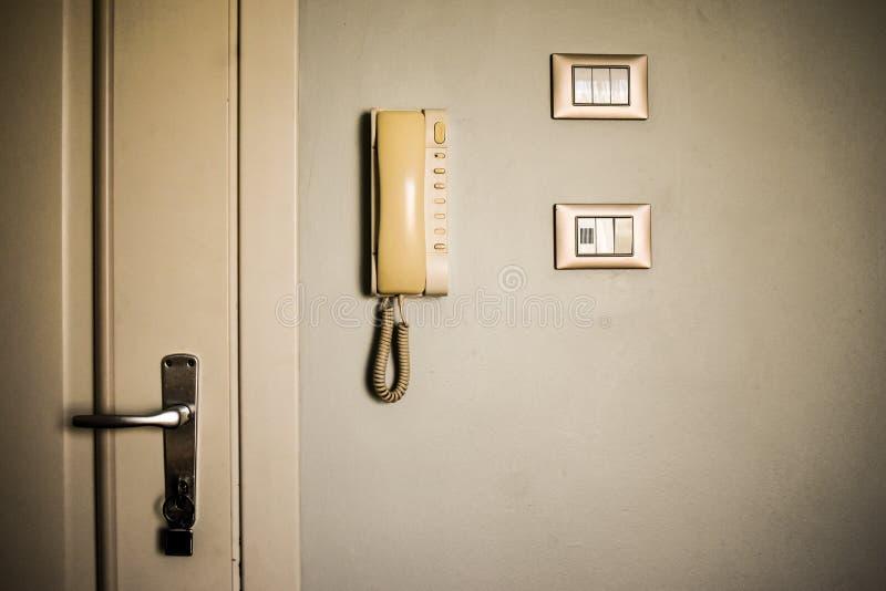 葡萄酒酒店房间设施 老开关和古色古香的电话在白色墙壁上 免版税库存照片