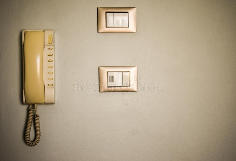葡萄酒酒店房间设施 老开关和古色古香的电话在白色墙壁上 免版税库存图片