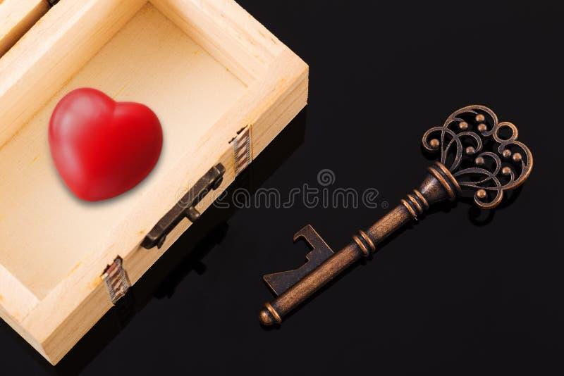 葡萄酒钥匙和红色心脏在宝物箱 免版税库存照片