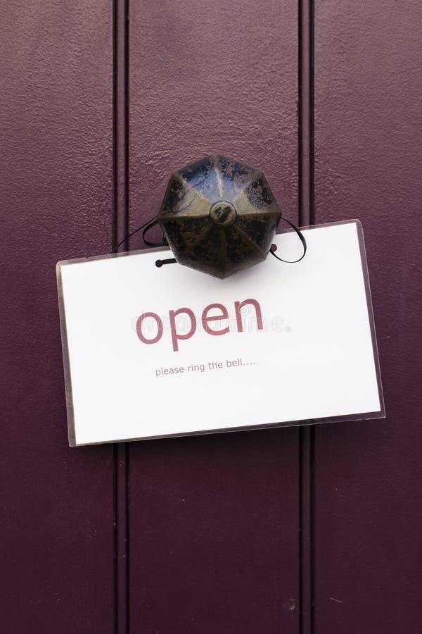 葡萄酒铜门把手的细节有开放标志的在一黑暗的purp 库存照片