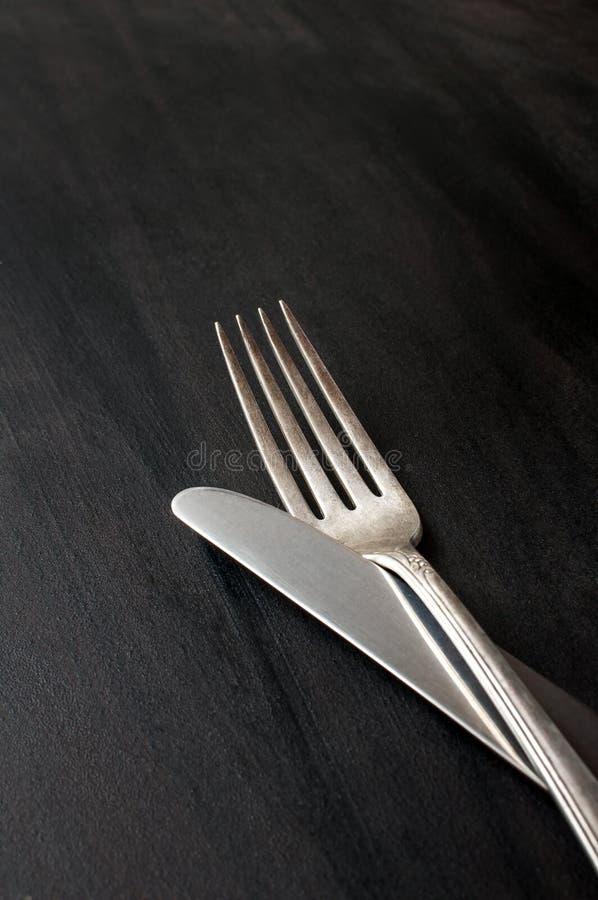 葡萄酒银色刀子和叉子在黑暗的背景,垂直的图象 库存图片