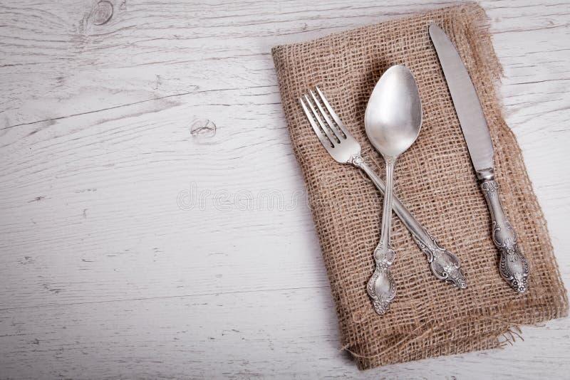 葡萄酒银色碗筷刀子、匙子和叉子在餐巾 库存照片
